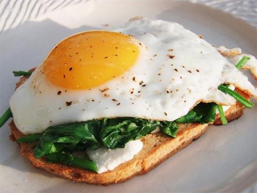 Huevos a la plancha y espinacas sobre tostada